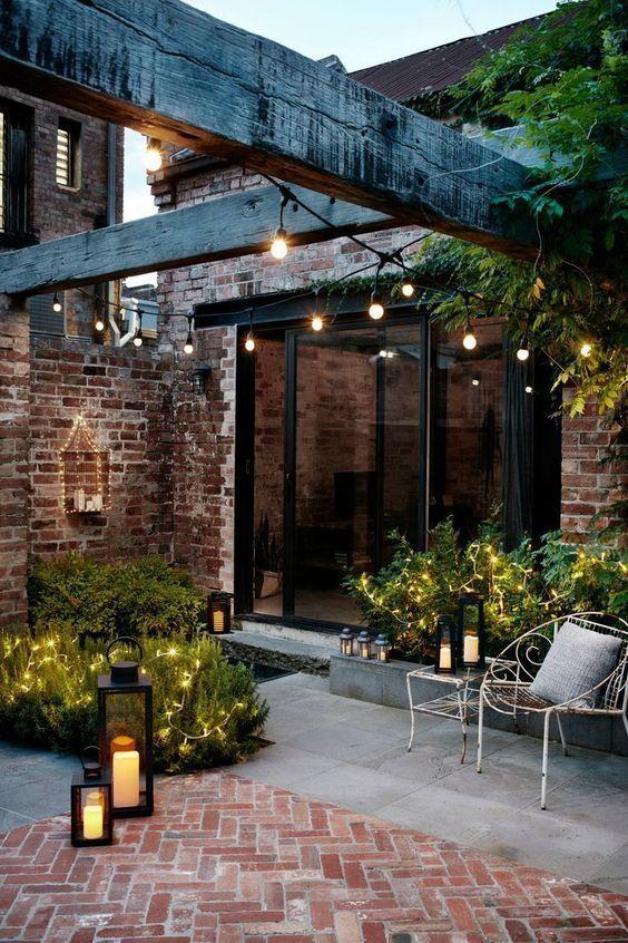 courtyard garden with garden lanterns and festoon lights Unique Outdoor Decorations For Summer Parties