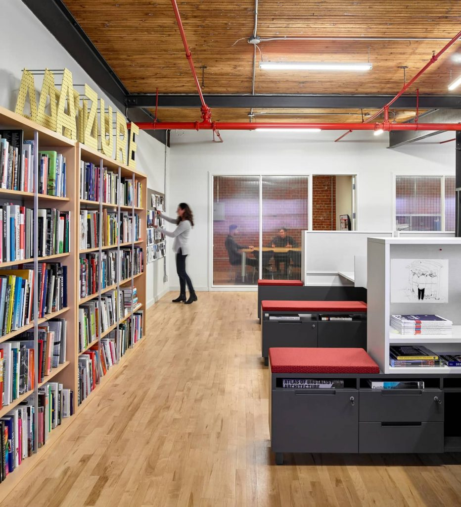 integrated bookshelves and storage cubbies 932x1024 An Old Transformer Factory Was Converted into a Bright Office