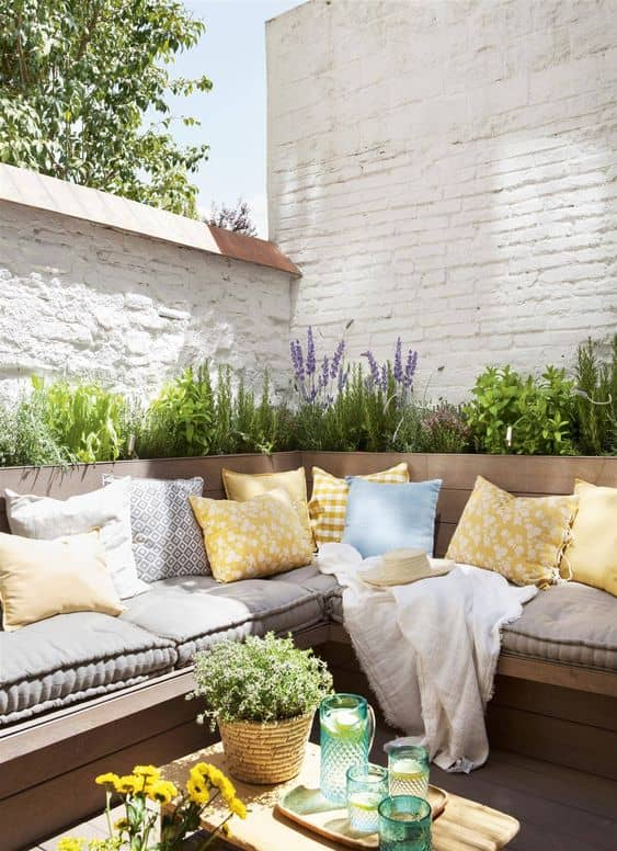 furniture and plants create a beautiful patio wall 14 Patio Wall Ideas That Will Make Your Outdoor Space More Attractive
