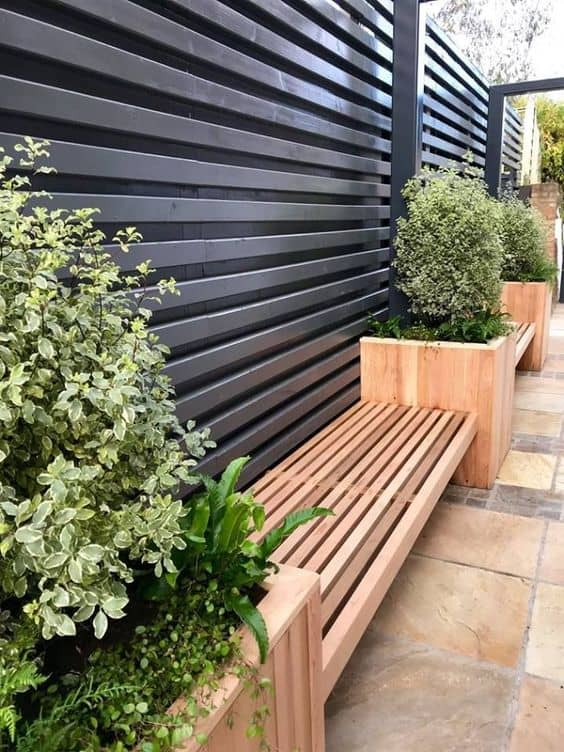 wooden cladding and seating area 14 Patio Wall Ideas That Will Make Your Outdoor Space More Attractive