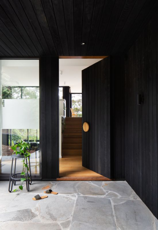 charred timber concealed door and blue stone paving The Beach House by Corke Design Studio