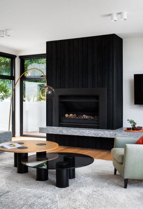 wood fireplace sitting on granite hearth The Beach House by Corke Design Studio